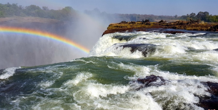 آبشار ویکتوریا در زامبیا زامبیا یک کشور آفریقایی است که طبیعت نابی را در خود جای داده است. یکی از اماکن دیدنی زامبیا آبشار ویکتوریا و استخر شیاطین میباشد که به دلیل زیبایی بینظیرش در فهرست امروز ما قرار گرفته است. باید بدانید که آبشار ویکتوریا لقب مرتفعترین آبشار دنیا را به دوش میکشد به همین خاطر حتما ارزش بازدید را دارد. آبشار ویکتوریا و استخر طبیعی آن تا سالهای زیادی از چشمان مردم جهان پنهان شده بود اما حالا به یکی از چالش برانگیزترین مکانهای دنیا برای گردشگران ماجراجو تبدیل شده است.
